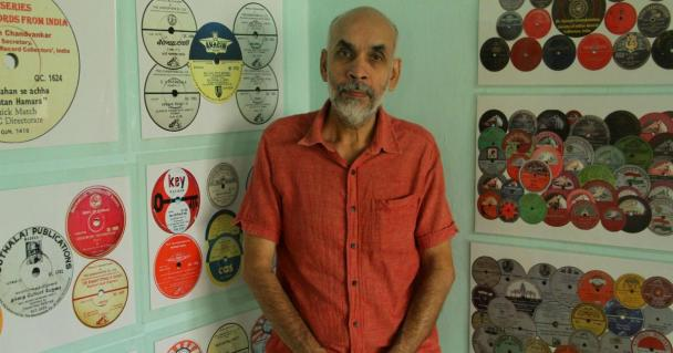Dr Suresh Chandvankar standing next to his collection of records