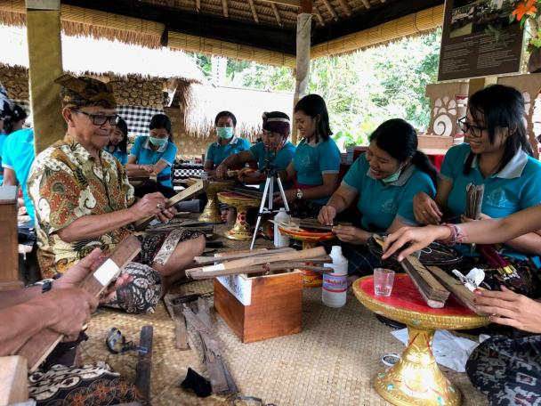 An elder with a group of young Indonesians look at palm leaf manuscripts