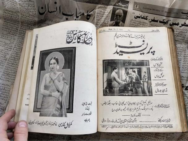 One of the magazines has been opened to show photographs of actors.