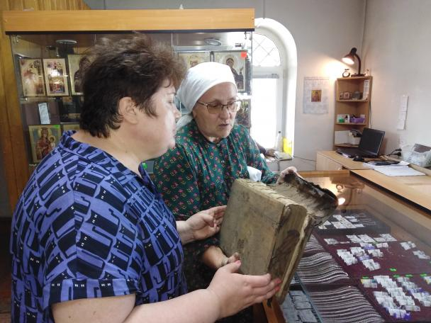 Two women looking at the broken spine of a book