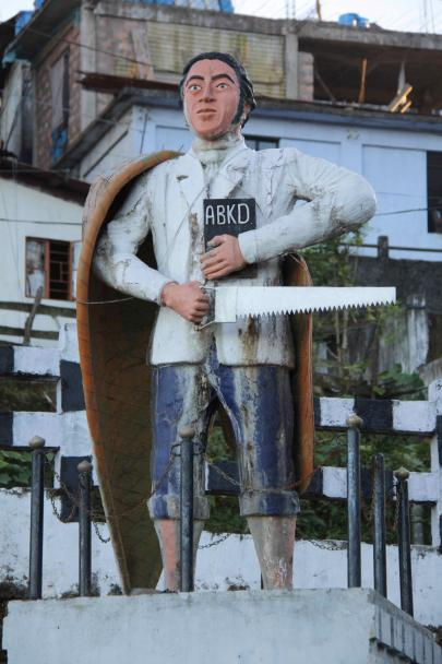 Painted statue of man with canoe on shoulder, holding a saw in one hand and in the other he has a book with 'ABKD' written on the cover.