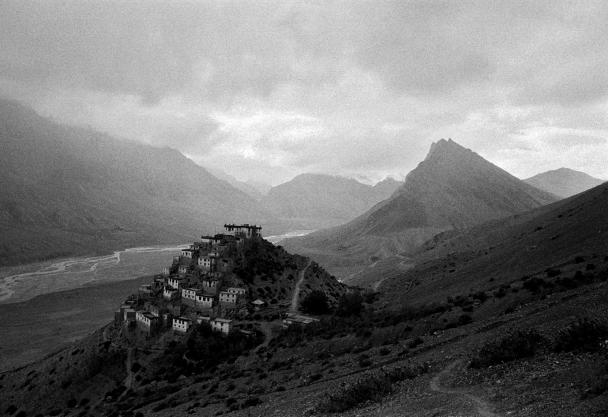 Black and white photograph of a village on a steep mountainside. Mountain tops are visible int he distance