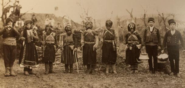 Photo of nine people wearing traditional costumes. Bulgaria.
