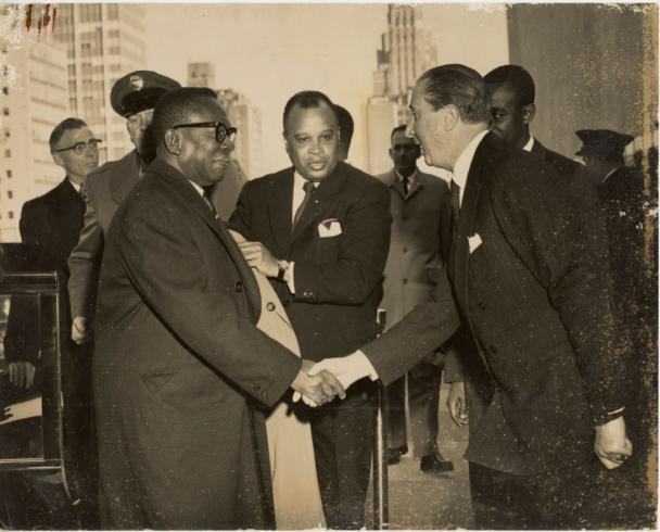 Former Liberian president William V. S. Tubman shaking hands with an unidentified man
